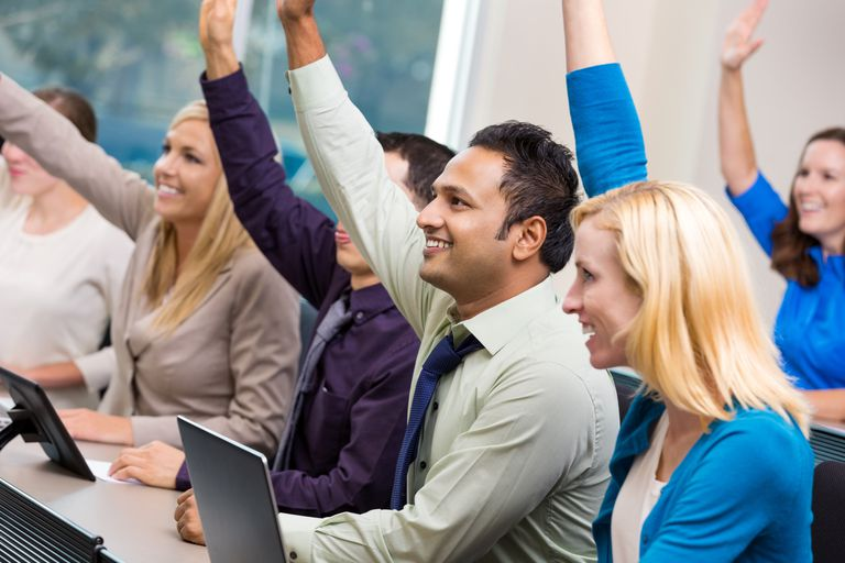 Diverse business people raising hands during meeting where they are developed, engaged, and retained.