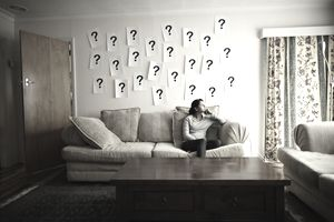 woman sitting on couch with question marks above her head