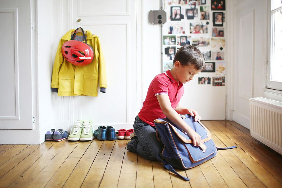 Boy filling his backpack for school.
