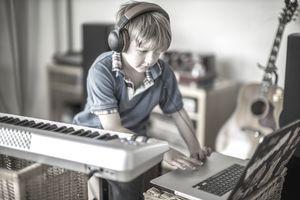 kid making music on laptop and keyboard