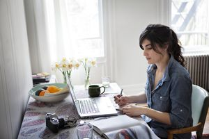 young woman writing at a laptop