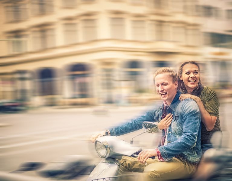 man and woman riding motor scooter