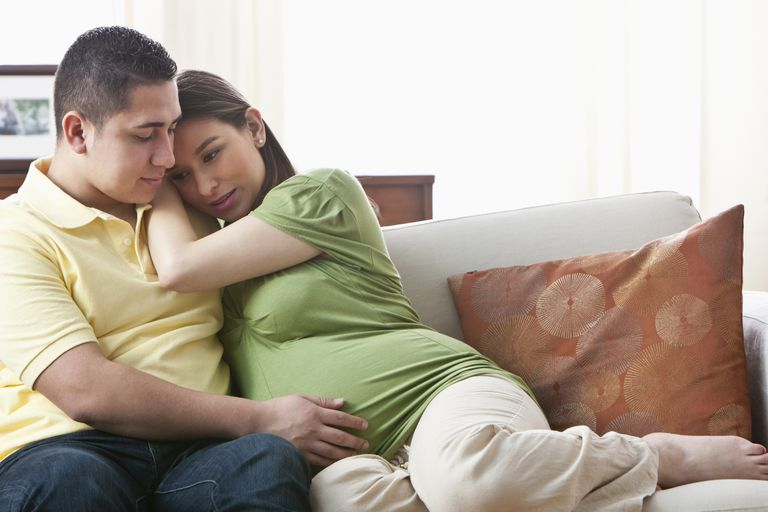 Hispanic man hugging pregnant girlfriend on sofa