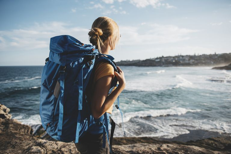 Woman backpacking by the ocean