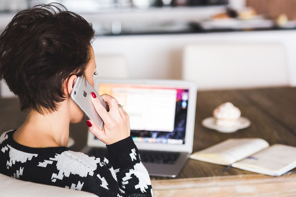 Productive woman talking on iPhone while using computer
