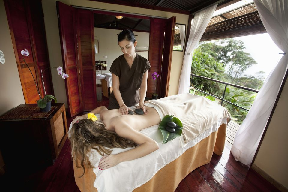 Massage therapist giving a hot stone treatment