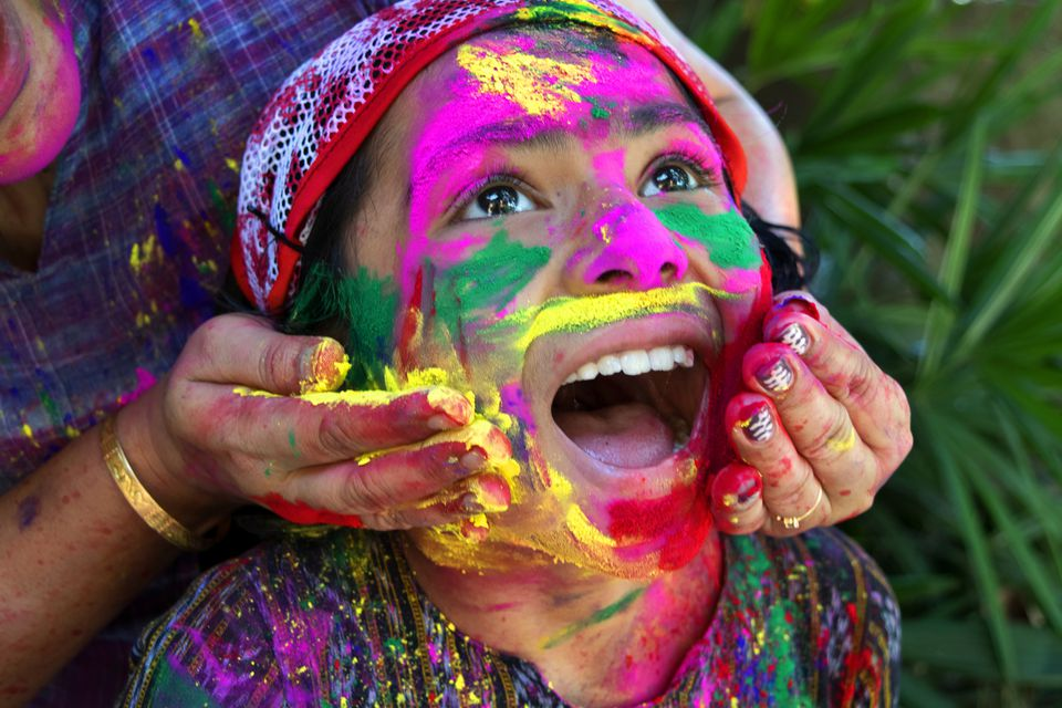 Girl smeared with colors during the Holi festival in India