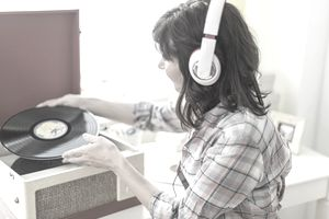 Woman listening to music on antique record player, Jersey City, New Jersey, USA