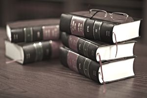 Stacks of law books on a wood table with eyeglasses