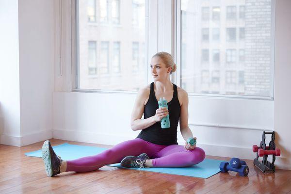 Model holding water bottle in fitness studio