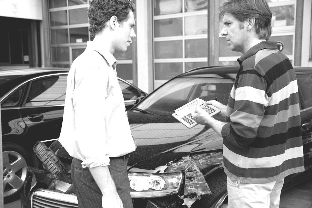 Insurance adjuster assessing damage to car