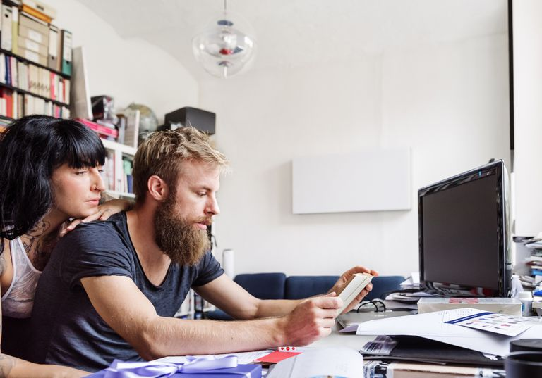 young couple reading in front of computer at desk
