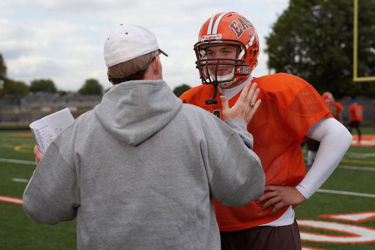 Teenage (16-17) American football player talking with coach