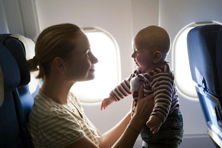 Mother and her baby boy playing on the plane