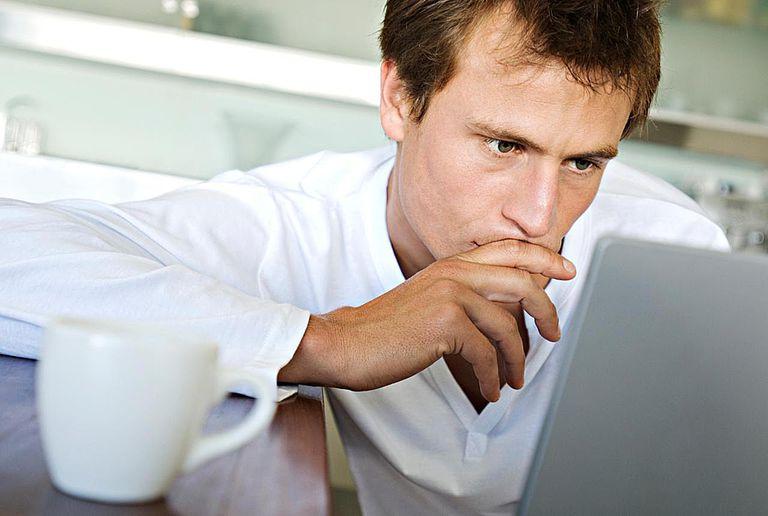 Man using laptop in kitchen