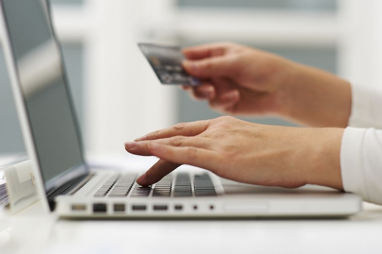 Closeup of hands, computer and credit card.