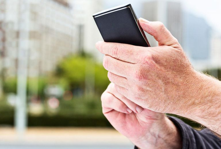 A man's hands touch the screen on a modern cellphone with an android operating system