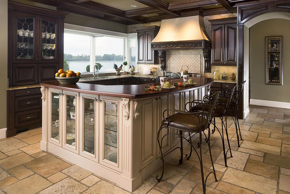 Traditional style home kitchen island with stone flooring.