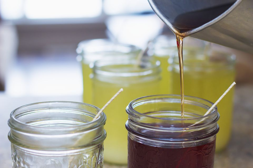 A pitcher is used to pour hot soy wax into glass mason jars with candle wicks for the final step in candle making for home made gifts