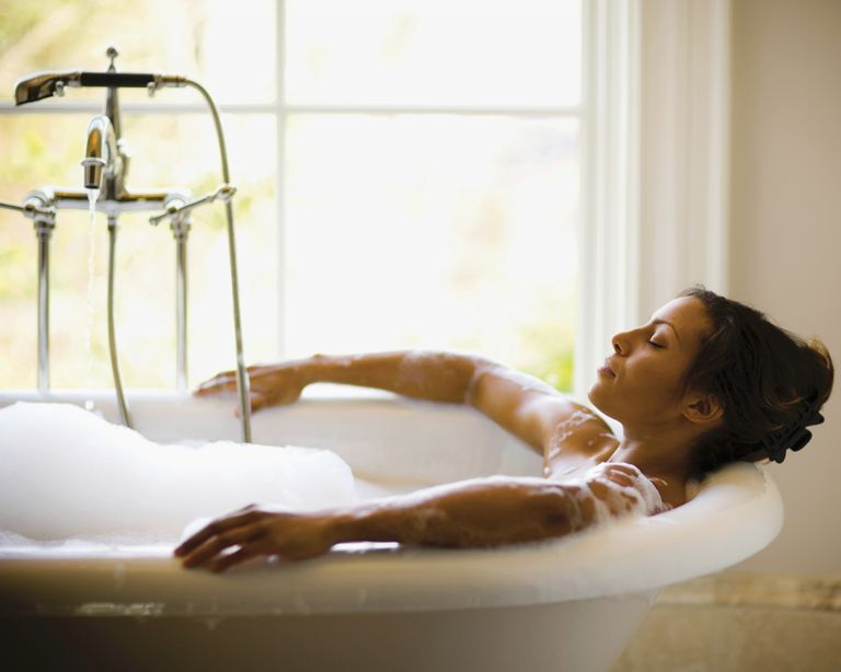 A woman relaxes in a bubble bath