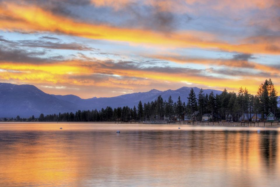 A brilliant fall sunrise is reflected in Lake Tahoe, California.