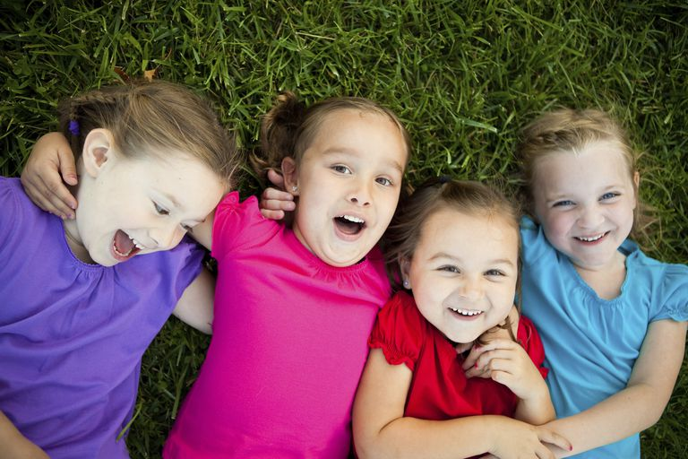 5 year old child development - girls lying on grass and laughing