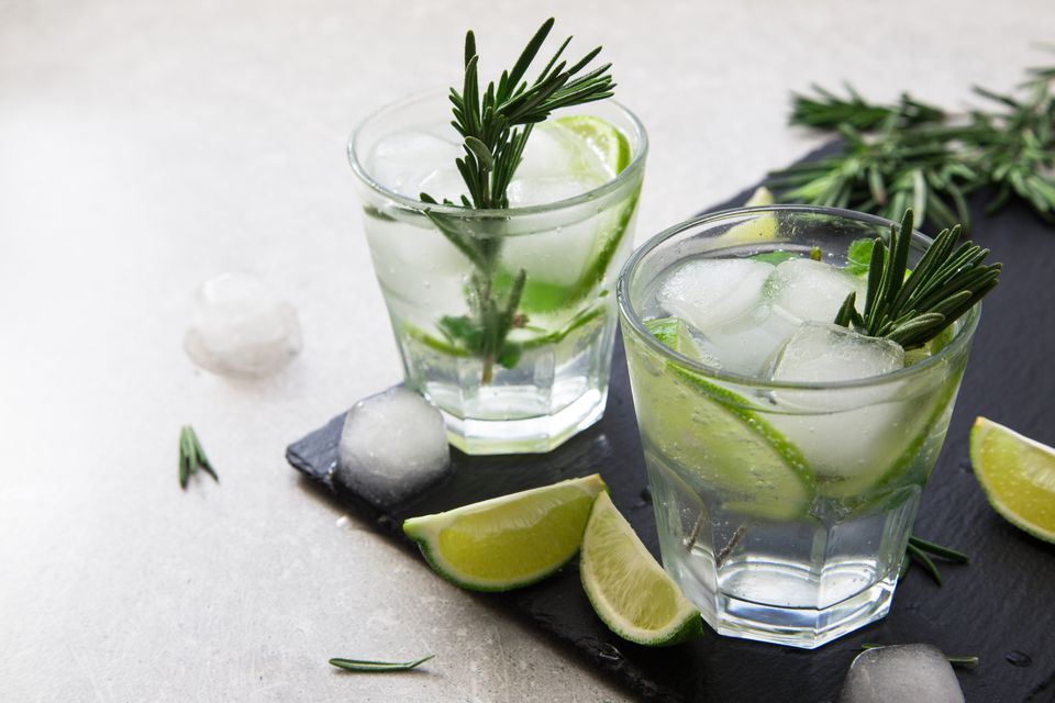 Gin and tonic with lime and rosemary on a slate board.