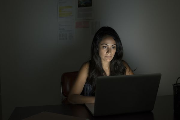 Woman sitting at computer in darkened room looking up egg donor ads