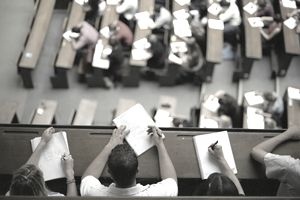 Students sitting in lecture theatre making notes