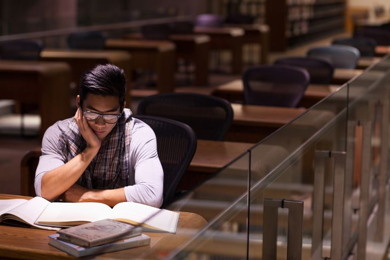 Student studying late in an empty library