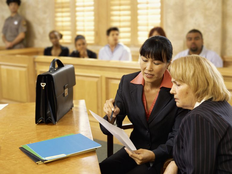 Side profile of a lawyer discussing the case with the witness