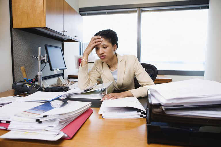 Businesswoman overwhelmed by work in office