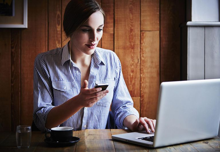 Young woman sitting in cafe holding smartphone, using laptop computer