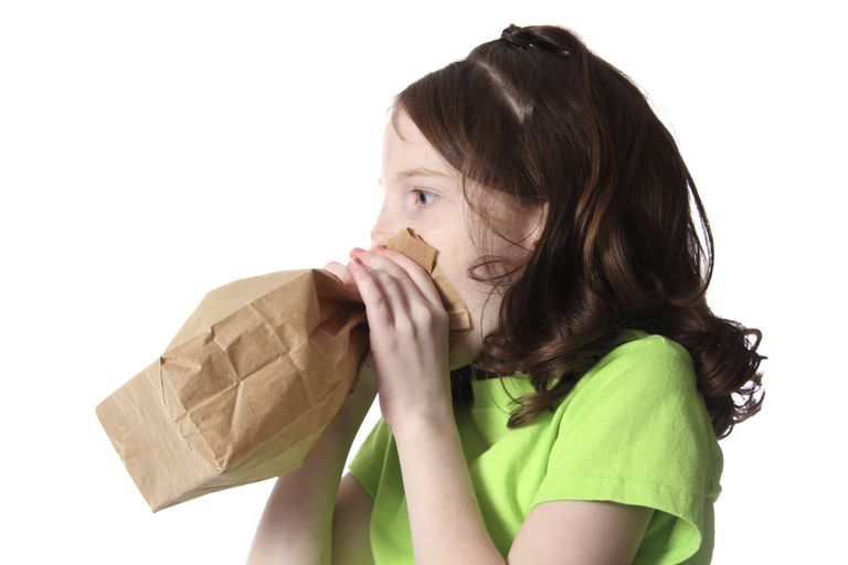girl breathing into a paper bag