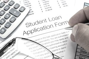 'Student Loan application Form with pen, calculator and writing h'