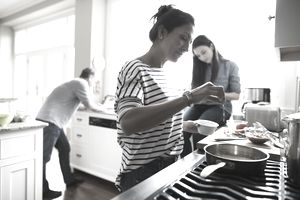 Woman cooking at stove in kitchen