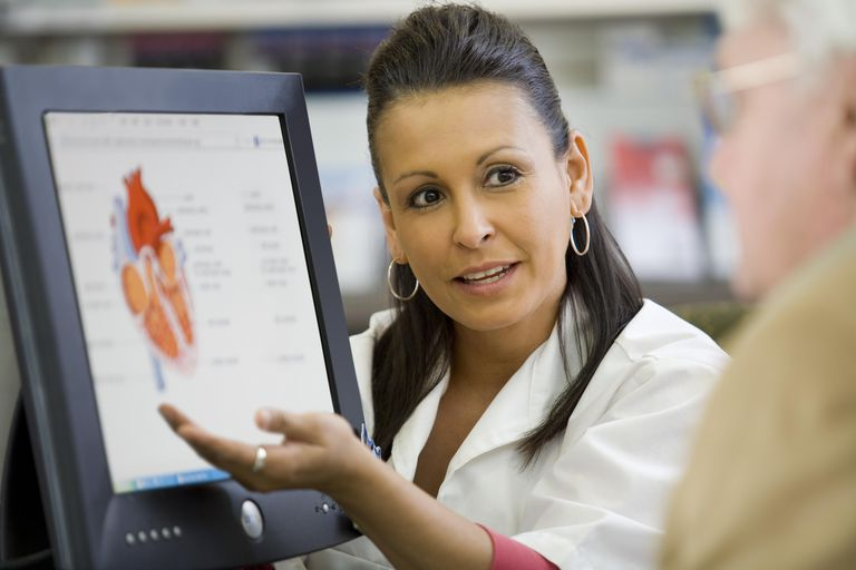 Pharmacist showing heart display on computer