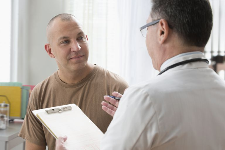 Caucasian soldier and doctor talking in office