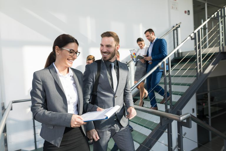 Group of business people walking down stairs and communicating