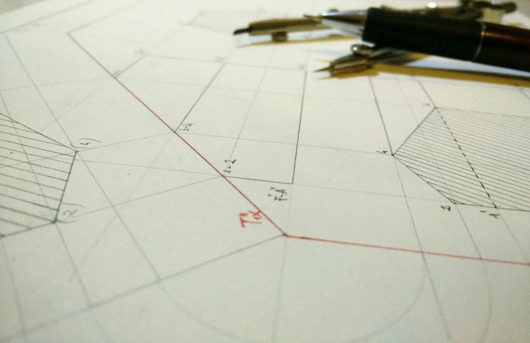 Close-Up Of Blueprint And Pen