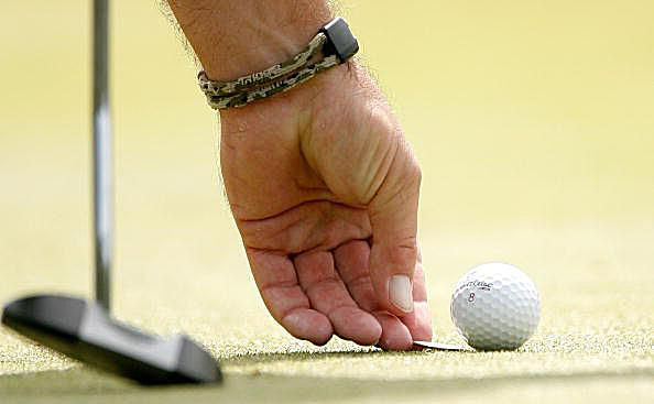 Placing ball marker behind golf ball on putting green prior to lifting ball