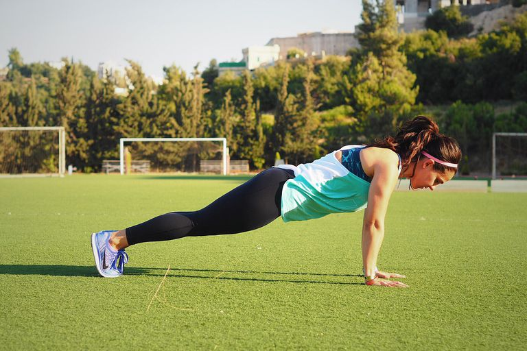 Woman doing a plank on field