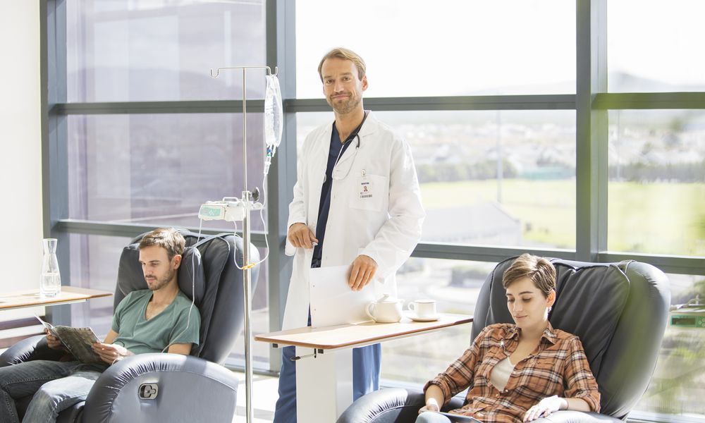 Doctor standing over patients receiving IV therapy