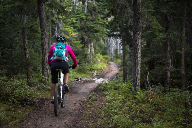 Woman mountain biking down a trail