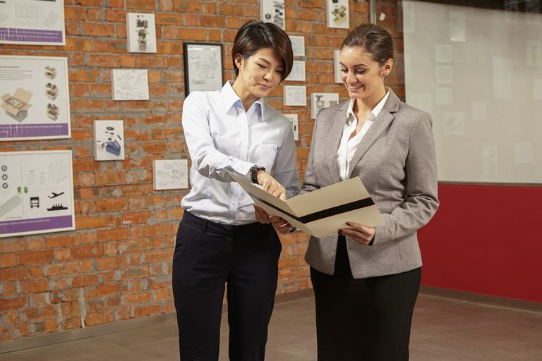 Female Asian worker showing Caucasian female manager print brochure in gallery of printing and packaging factory, China