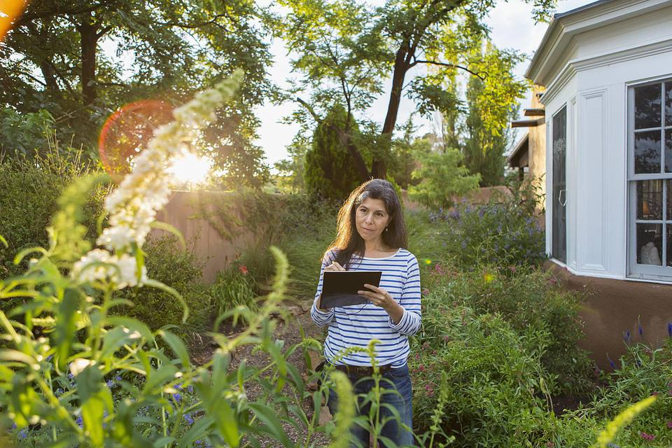 Hispanic woman sketching flowers in garden