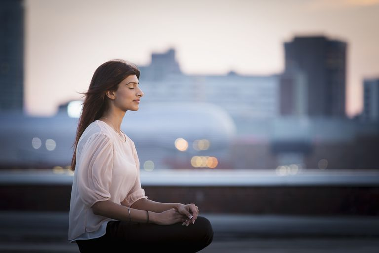 Woman meditating on rooftop