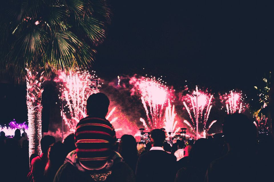 Rear View Of Father And Son Enjoying Firework Display During New Year Eve