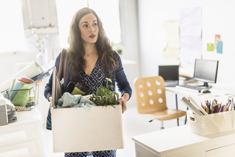 woman employee leaving office with box of belongings