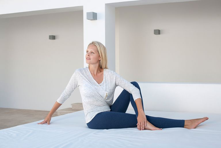 Young woman doing spinal twist pose on bed outdoors